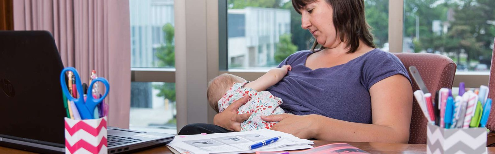 Woman breastfeeding baby at work