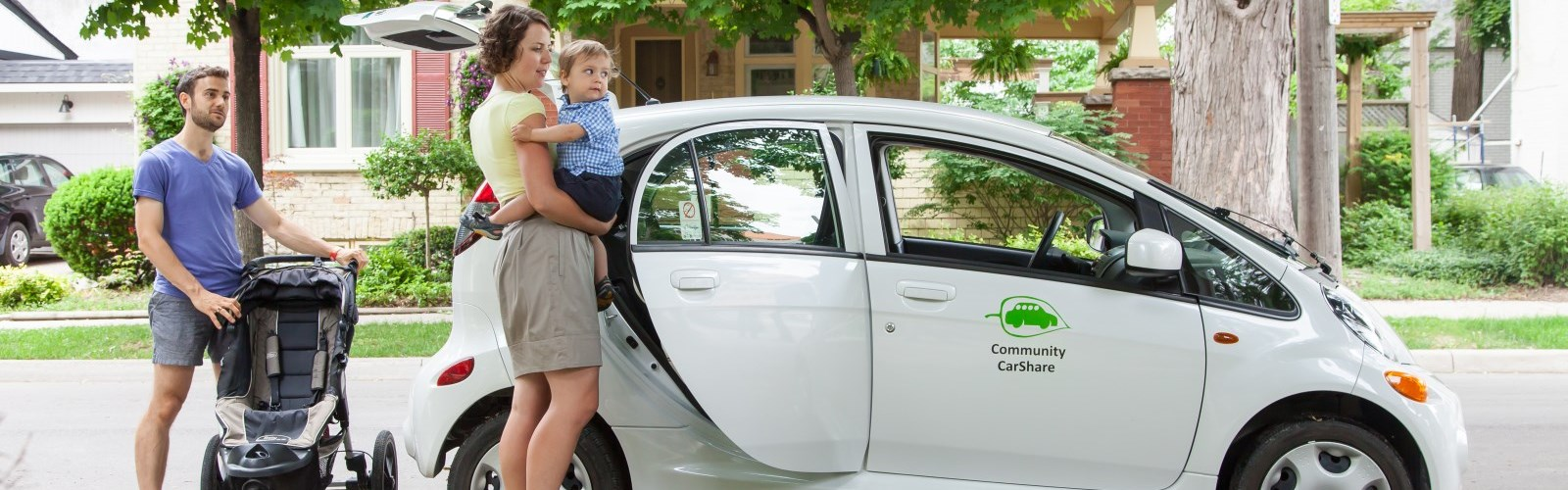A picture of a young couple with a baby getting into a Community CarShare vehicle