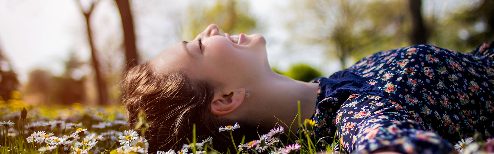 woman lying down on grass with eyes closed