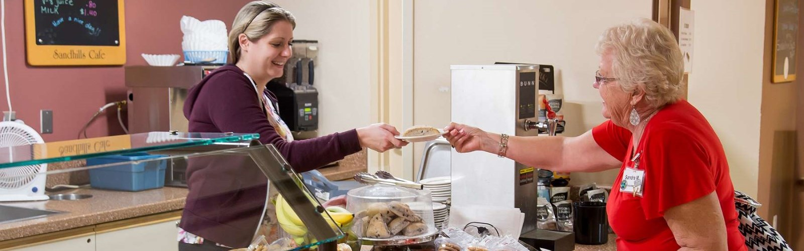 Volunteer serving food to client in the cafe on Sunnyside campus