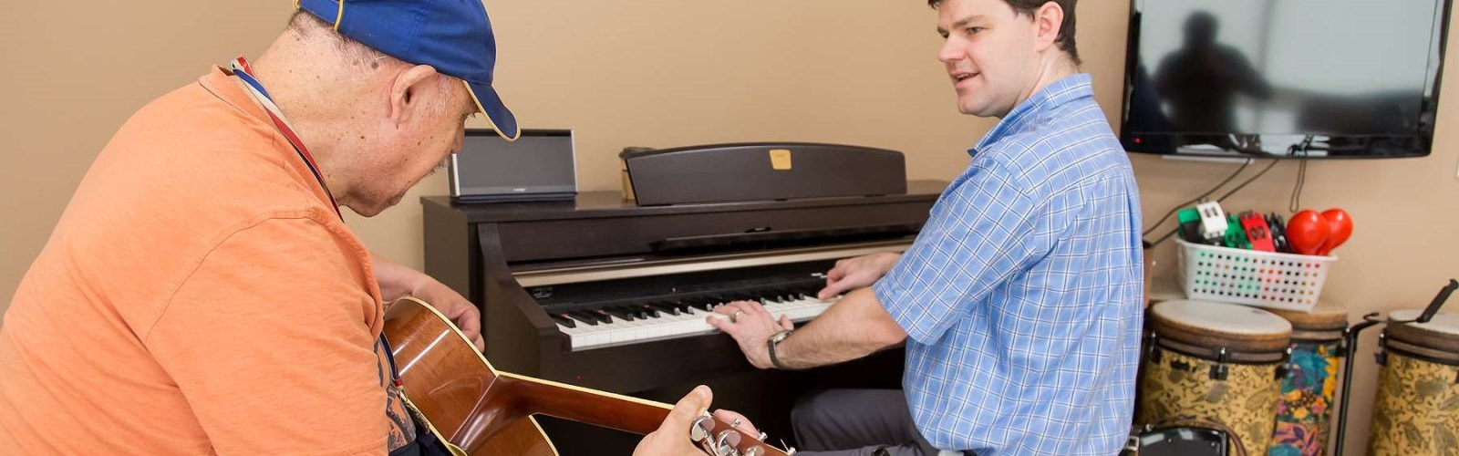 Music therapist plays piano next to older adult playing guitar.
