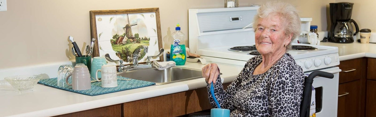 Sunnyside Supportive Housing resident in wheelchair cleaning dishes next to her sink.
