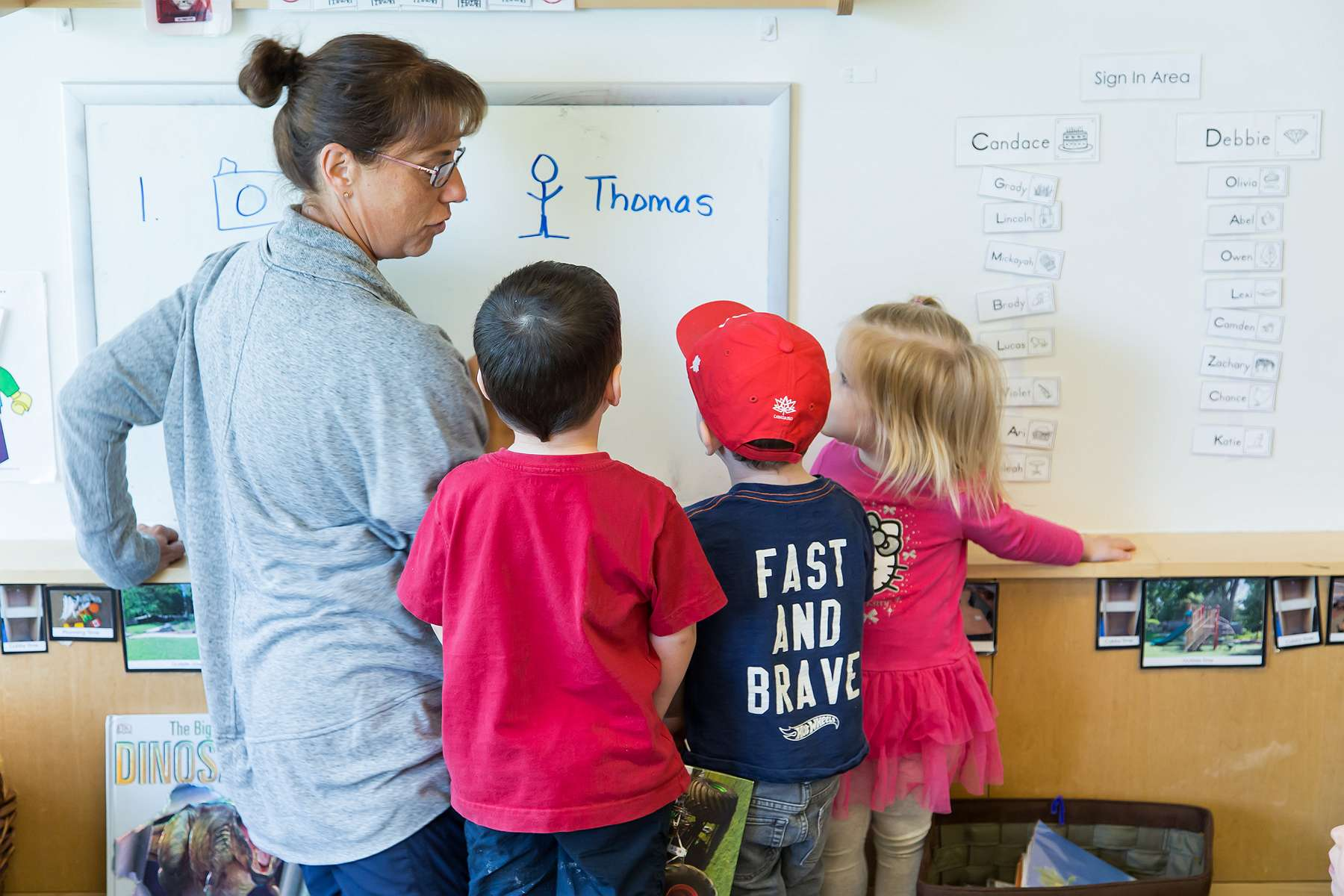 Image of educator interacting with three children at the whiteboard