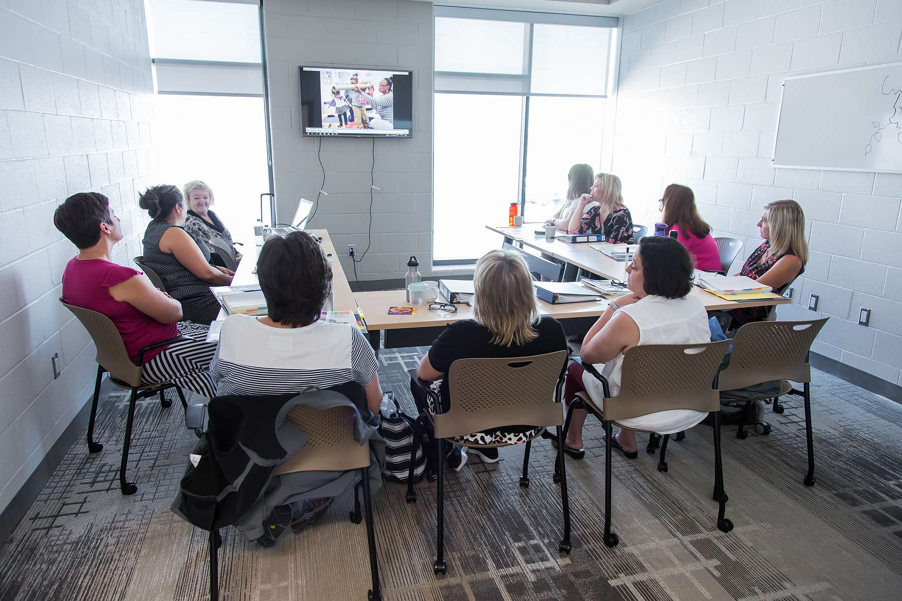 Image of educators gathered around table watching a video on how learning happens.