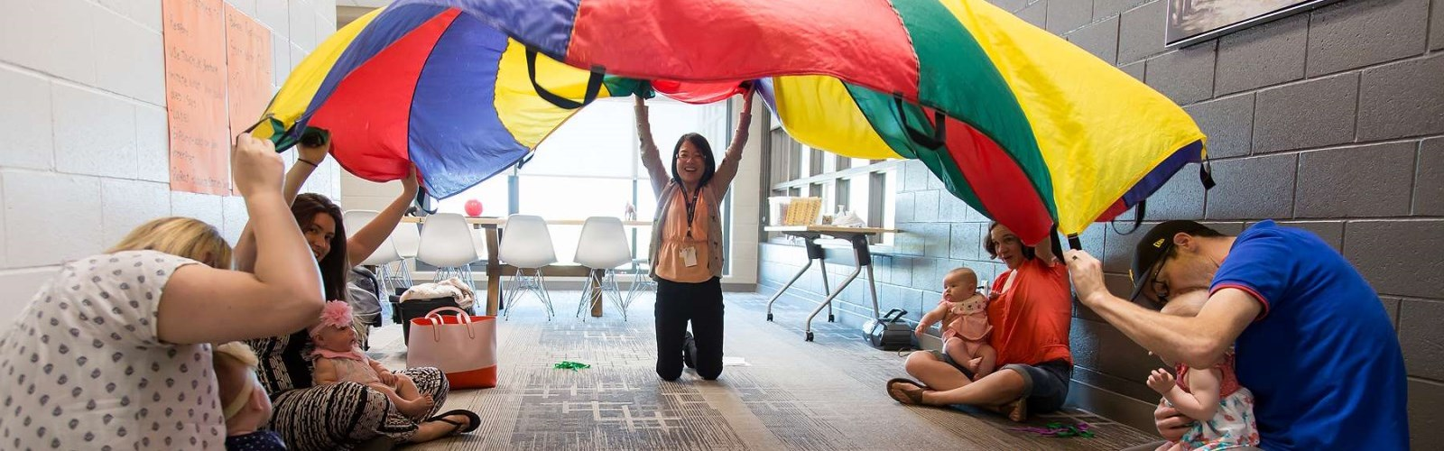 Children and their parents playing with a parachute at the Elmira EarlyON child and family centre.