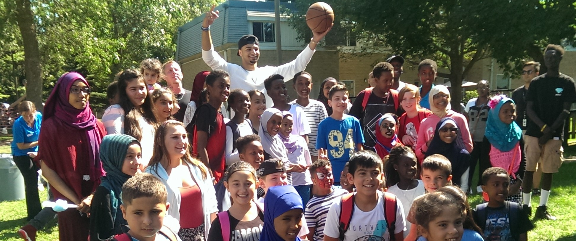 Image: Children gathered around NBA player Jamal Murray at barbecue in community housing
