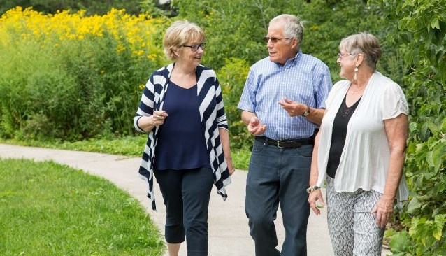 A male older adult and two female older adults walk along a path in a park.