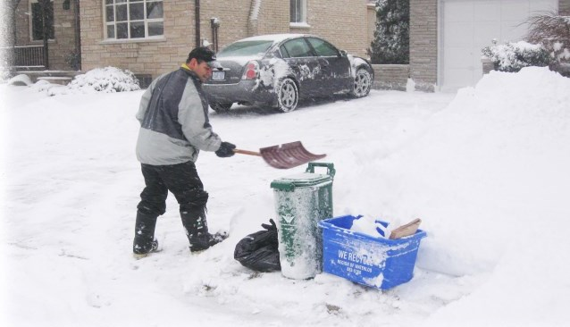 Shovelling a shelf in the snow for collection containers