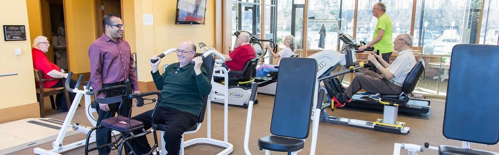 Older adults working out on the treadmill and equipment inside Sunnyside Wellness Centre.