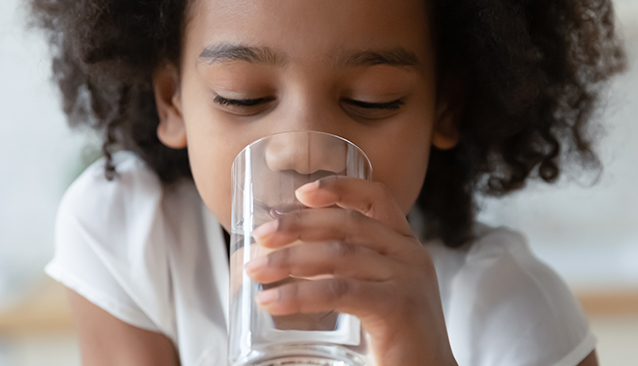 child drinking glass of tap water