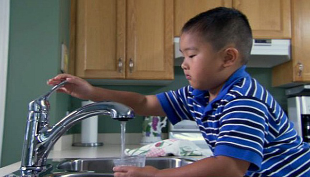 boy filling glass with water from tap