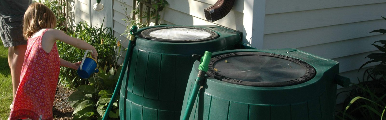 child watering plants with watering can beside rain barrels