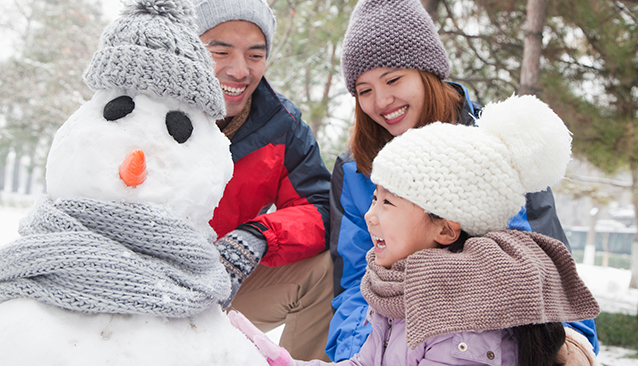 parents with daughter building a snowman