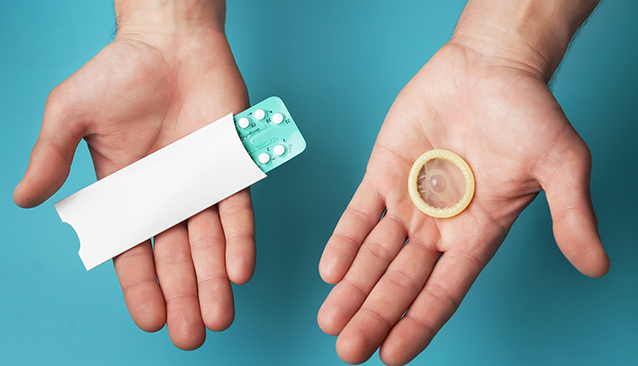hands holding contraception pills and condom